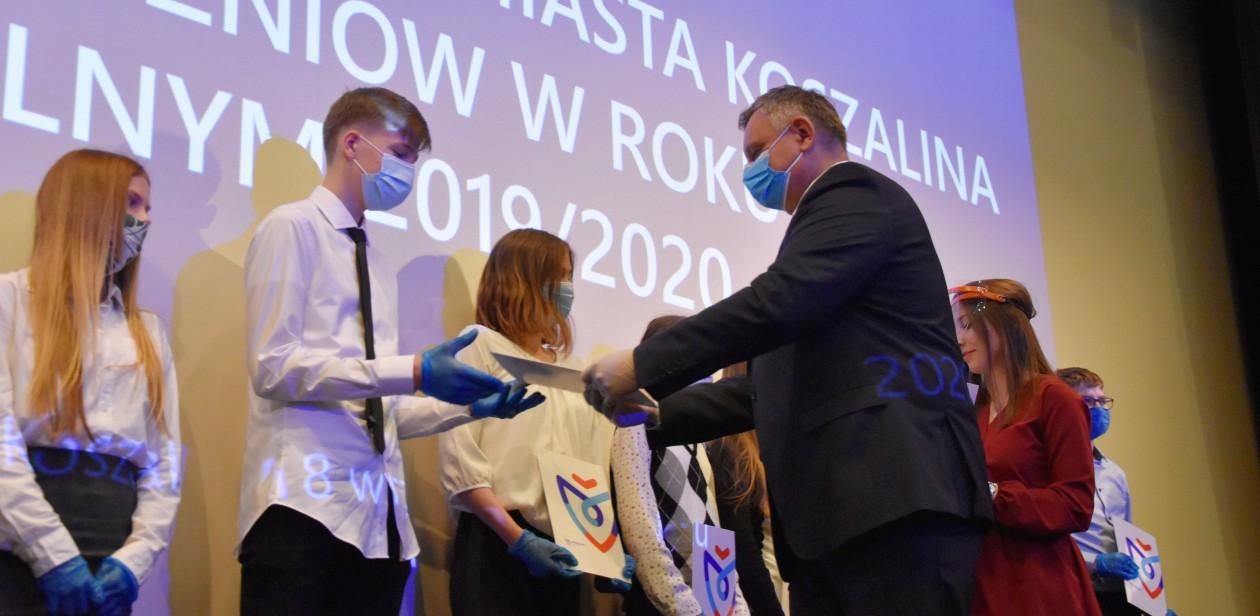 Na zdjęciu znajduje się prezydent Miasta Piotr Jedliński wręczający nagrody dla najlepszych uczniów z koszalińskich szkół
