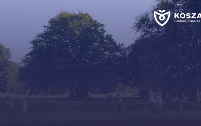 Na zdjęciu przedstawiony jest park z drzewami oraz logo Koszalin Centrum Pomorza